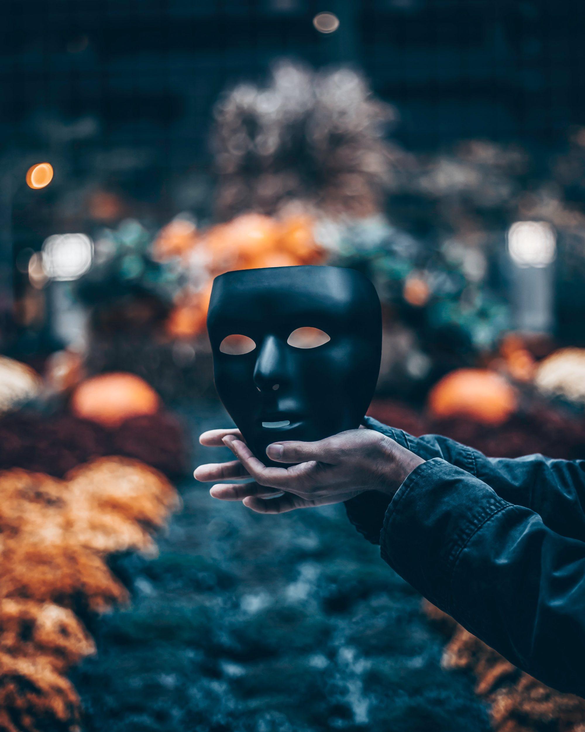 Schwarze Maske in Händen