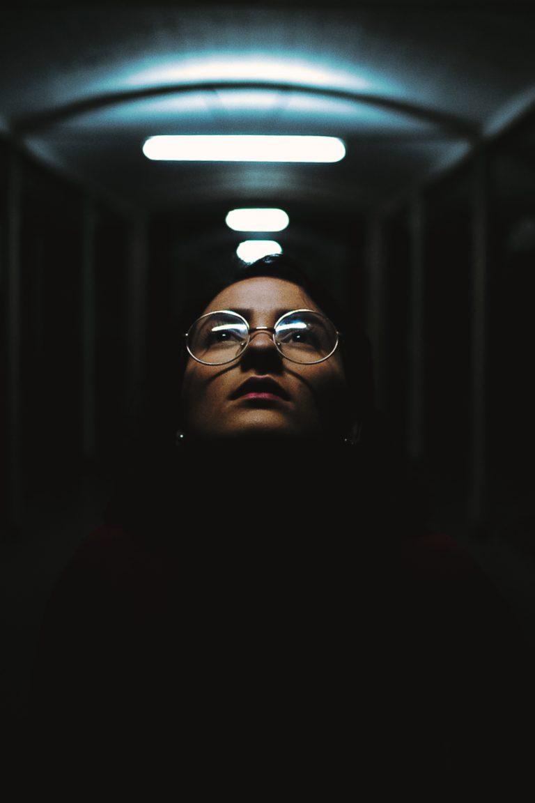 Frau unter Neonröhren