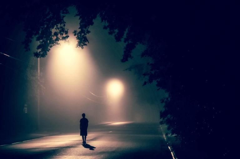 Person alleine im Dunkeln auf der Strasse
