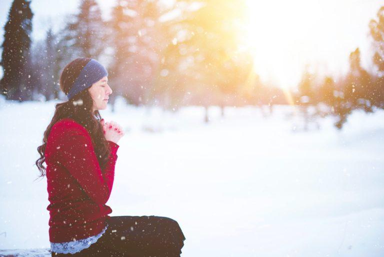 frau betet im schnee