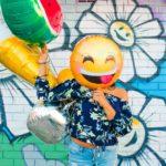 Frau hält Smiley-Emoji-Luftballon vors Gesicht