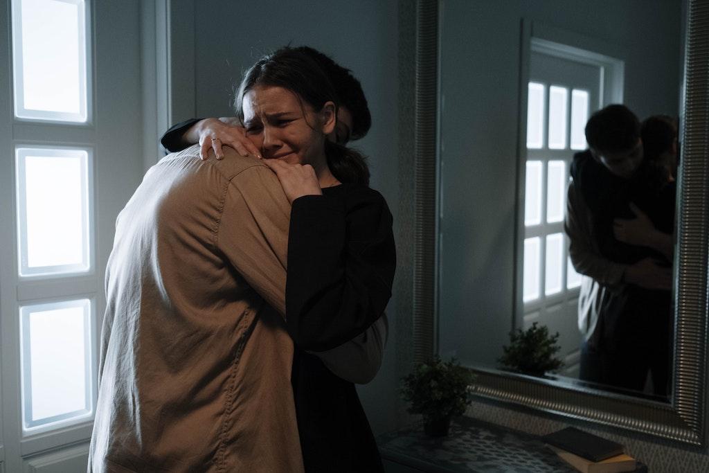 junge Frau weint und umarmt Person
