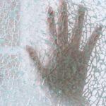 Hand berührt von hinten eine zersplitterte Glasscheibe