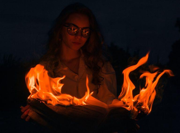 Frau mit Sonnenbrille hält brennende Zeitung, dunkler Hintergrund