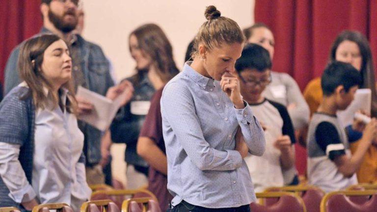 Junge Frau, Julie Rodgers, im Gebet versunken, im Hintergrund Menschen bei einem Gottesdienst