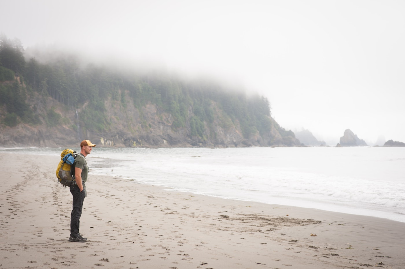 Mann mit Rucksack steht an einem Meeresstrand, neblige Stimmung